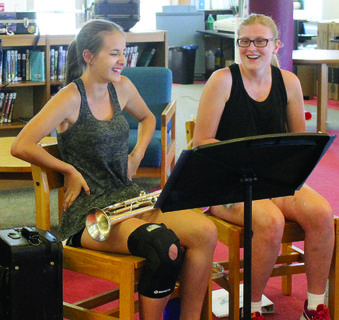 "Emily Durbin does ""La Macarena"" to the beat of the song while Abby Russell laughs during a brass section practice."