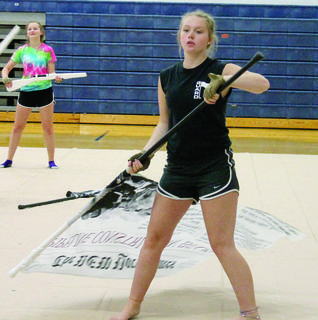 Peyton Louden practices with a flag during color guard practice.