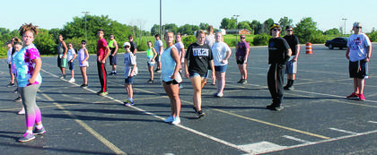 The marching band works on their form during band camp.