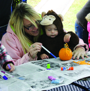 Heather Monhollen and her son, Brycen Monhollen, color on a mini pumpkin before monkeying around during a cold afternoon.