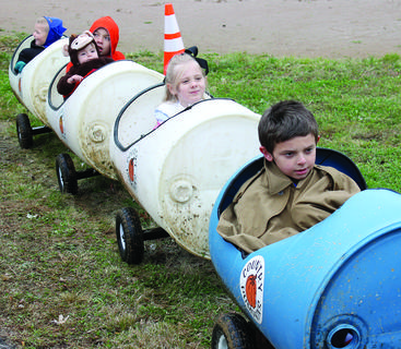 Left to Right: Gabe Brown, Evie Dreyer, Hunter and Brycen Monhollen and Brantley Monhollen take a ride on the Country Pumpkins barrel train through the muddy baseball field during the 31st annual Halloween in the Park at Piddle Park in Dry Ridge Oct. 28. Kids got to walk the candy line, decorate pumpkins, take photos with backdrops, enter a costume contest and listen to spooky stories during this year's chilly event. The event is sponsored by the Grant County News and the City of Dry Ridge.