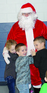 MCE's Izabella Collins, Michael Ford and Rand Sexton wouldn't let go of Santa after lunch.