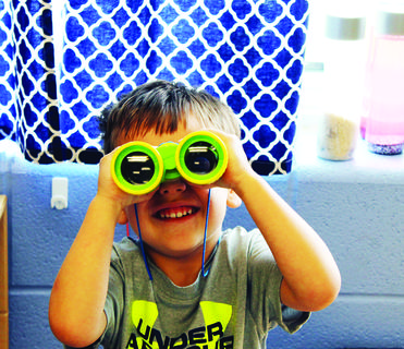 SES preschool Jace Neimann looks through binoculars.