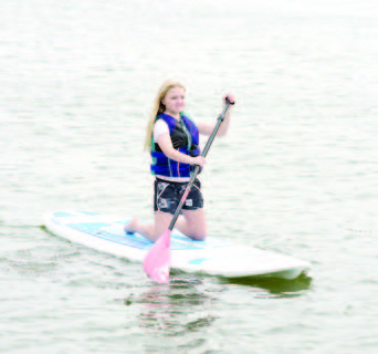 Katie Zwick balances on her knees while paddling the lake.