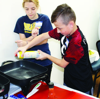 Keaton Conley and Grace Barnes focus on spraying a pan.