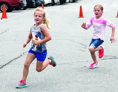 DRE's Laela Cook and Mattie Brinker round the corner in a long running relay during track and field day May 17. These two girls led the pack in their class during the run in the parking lot behind Dry Ridge Elementary before it started raining.