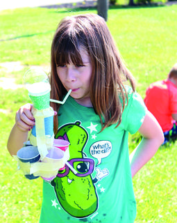 Lane Flerlage focuses on blowing bubbles with a homemade contraption with Dixie cups.