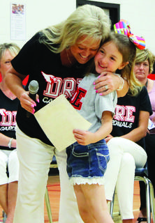 Lauri Ford gives Annabelle Stacy a congratulatory hug. Photos by Camille McClanahan