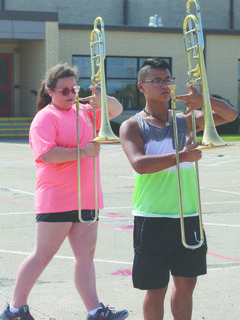 Kailani Albert and Liam Funk practice marching with their instruments.