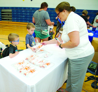 Nancy Howe, Public Information Officer for Grant County School District, hands out school supplies to students.