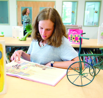 Lydia Chadwick looks through a book in the new section of the library.