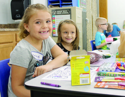 MCE students Harleigh Caudill and Sandra Volker get their school supplies out before class begins.
