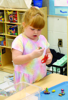 MCE preschooler Haylee Edwards enjoys free time activities. Haylee was cutting up bits of Playdoh in the arts and crafts corner.