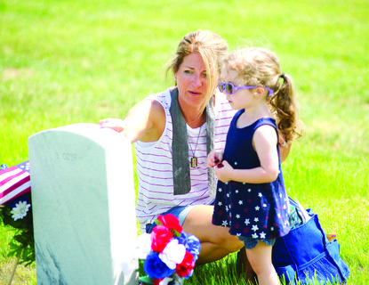 Katrina Prysi teaches Sophia Prysi about Memorial Day and placing peonies at the headstones in the cemetery on Memorial Day, May 28, at Kentucky Veterans Cemetery North in Williamstown.