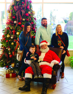 Storm, Paige and Gus Mason, along with Emily Hampton, pose for a photo with Santa Claus.