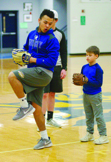Grant County Braves baseball player Damion Ingguls helps Jaxxon Turner in his form at the pitchers mound.
