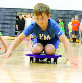 MCE's Owen Holt propels himself on the gym floor on a scooter board during an intense team relay event.