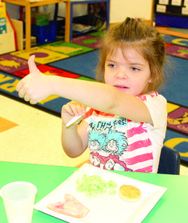 WES student Zoie Buchanan gives a thumbs up as she eats green eggs and ham.