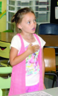 """WES student Madelyn Sanders says the """"Pledge of Allegiance"""" during morning announcements."""