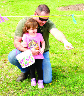 Raymond Preston points out an egg to Ivey Preston at the Easter Egg Hunt held at the Grant County Library.