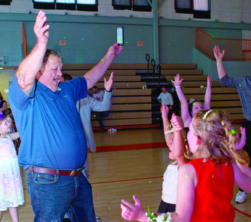 Herb Furnier performs the YMCA dance with his granddaughter, Chloe Kinman and her friends.