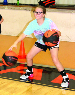 Cade Adams, left, and Taylor Masters, right, work on their dribbling skills during a basketball camp hosted by Williamstown High School.