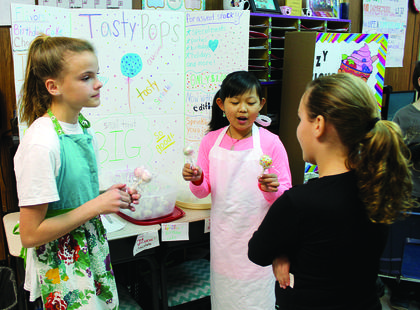 DRE fifth graders Lailah Whitton and Ella Lee attempt to sell their Tasty Pops to student customers.