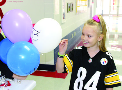 CMZ student Kaydence Brown pops a balloon to see what prize she won after finding one of 100 rocks hidden around school.