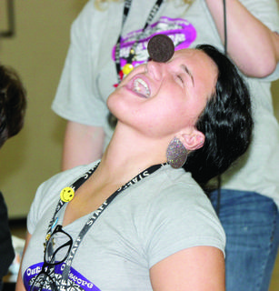 """Haley Cox, a  third grade Williamstown Elementary teacher, was the first competitor to inch an Oreo cookie from her forehead to her mouth during the KREP pep rally with """"Survivor"""" winner Nick Wilson."""