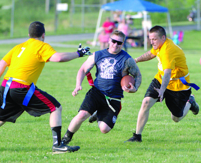 COPS vs. COACHES — GCSO's Tyler Robinson evades coach Brandon Taylor. The Grant County Youth Athletic Association raised almost $5,000 for youth football at the event.