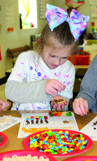 WES student Skylar Combs counts out pieces of trail mix for the 100th day of school.