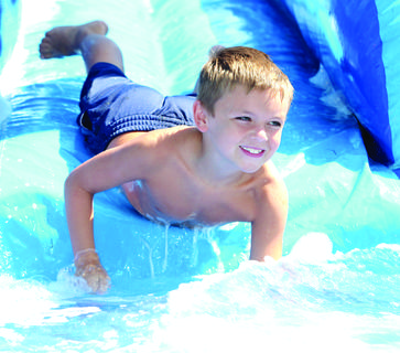 Michael Witt smiles as he splashes into water on the slide at Grant County Parks and Recreation's Summer Splash camp at Grant County Park in Crittenden.