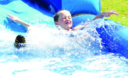 Dallas Clark hits the water fast at the end of the slide during Summer Splash camp.