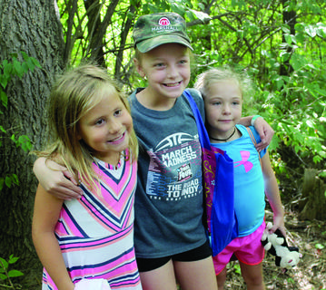 Reagan Hoehn, Mandy Dodds and Briley Good pose for a photo during a 4-H scavenger hunt on the park trail. Photos by Bryan Marshall