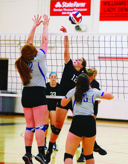 Brooklyn Perkins attempts to spike the ball past Lady Bearcat blockers.