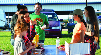 Several campers stand around a table to get their dinner while camping over the weekend.
