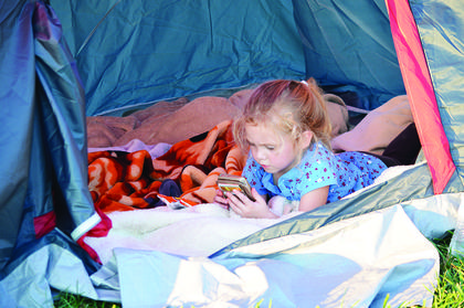 Taylor Threlkled of Williamstown plays a game in her tent until the outdoor games are set up to play. Photos by Ashley and Stacey Owen