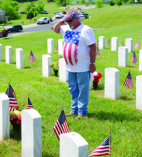 Above, U.S. Army veteran (1983-86) Greg Rapp salutes Jake Burgess' gravesite at the Kentucky Veterans Cemetery North.