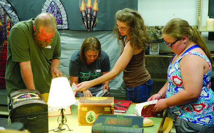 """Steve and Bridgette Lilly and Julie Hutchinson participate in a """"Harry Potter' themed escape room at the Grant County Public Library on July 14. Photos by Mark Verbeck"""
