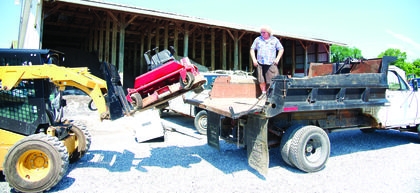 Tim Lang of Florence loads up mowers he purchased from the surplus auction June 29. Photos by Mark Verbeck