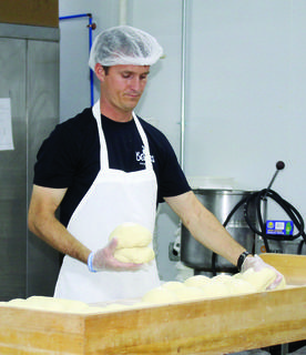 Troy Arnold works on separating dough for baked goods while