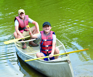 Tucker Ammerman and Gavin Scroggins take out the canoe during North Central  4-H Camp. A hundred campers, two junior counselors and 15 adult counselors made the trip to Carlisle . Photos by Ashley Owen
