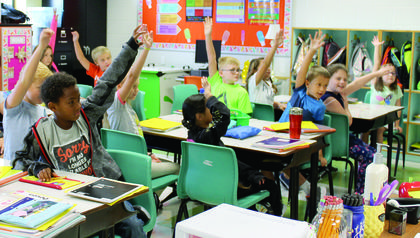 WES students raise their hands to volunteer for an activity at the Smartboard.