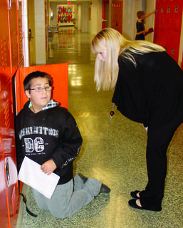 WMS student Keith Maynard talks to Leopold Moore, a teacher, while changing out books in his locker.