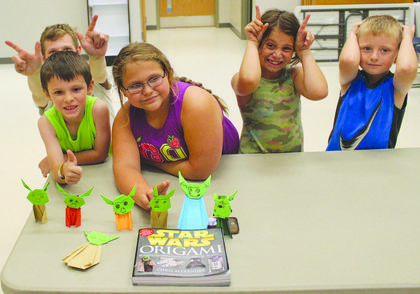 Children show off their handmade Yoda origami they learned at a library event.